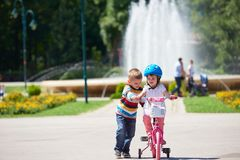 Boy and girl in park learning to ride a bike Royalty Free Stock Photos