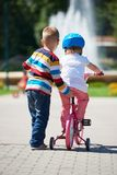 Boy and girl in park learning to ride a bike Stock Image