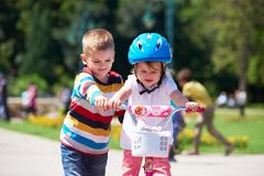 Boy and girl in park learning to ride a bike Royalty Free Stock Photo