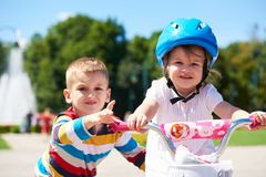 Boy and girl in park learning to ride a bike Stock Photo