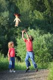 Boy and girl in park toss up upward  doll Stock Image