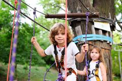 Boy and a girl pass an obstacle course in a rope park stock images