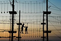 Boy and girl pass the obstacle course. At sunset stock image