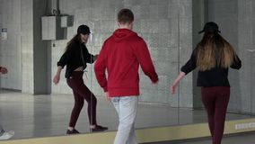 Boy and girl performing modern dance movement. Two modern dancers practicing dance moves near mirror. Lesson of contemporary dance stock footage