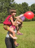 Boy and girl play. With colored air-ball solar daytime Stock Photos