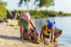 Boy and girl play and build a sand castle on the beach Stock Image