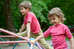 The boy and the girl play a children's playground. Summer Stock Photos