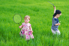 The boy and the girl play on green meadow. Kids hold in hand rackets for game in tennis Stock Photography