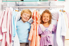 Boy and girl play hide-and-seek in clothes. Positive boy and girl play hide-and-seek in clothes together while shopping in the clothes store Royalty Free Stock Photos