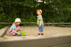 The boy and the girl play a sandbox. In a park Royalty Free Stock Photos