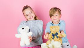 Boy and girl play with soft toys teddy bear on pink background. Bears toys collection. Teddy bears help children handle. Emotions and limit stress. Siblings royalty free stock photo
