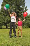 Boy and girl play in solar daytime. Boy and girl play with colored air-ball in solar daytime Stock Images