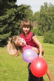 Boy and girl play in solar daytime. Boy and girl play with colored air-ball in solar daytime Royalty Free Stock Image