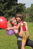 Boy and girl play in solar daytime. Boy and girl play with colored air-ball in solar daytime Stock Photo