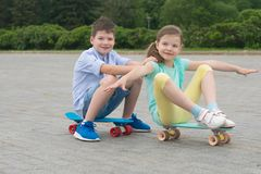 Boy and girl play on sport boards, roll behind each other stock photos