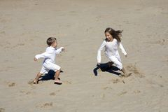 Boy and girl play together at the beach Stock Photos