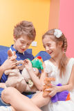 Boy and girl play with toys. Happy play. Close-up of a cute small girl and a boy playing with toys and laughing loudly Royalty Free Stock Photo