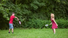 Boy and girl playing badminton stock video