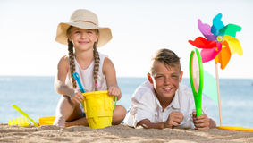 Boy and girl playing beach. Happy two kids in elementary school playing with toys on beach on summer day royalty free stock photography