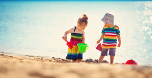 Boy and girl playing on the beach Stock Images