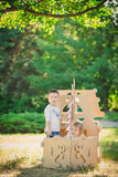Boy and girl playing in a cardboard boat Stock Photos