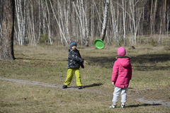 Boy with a girl playing in a clearing in the woods they throw th Stock Photo