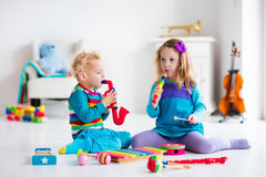 Boy and girl playing flute. Children with music instruments. Musical education for kids. Colorful wooden art toys. Little girl and boy play music. Kid with Stock Image