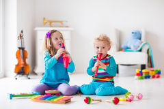 Boy and girl playing flute. Children with music instruments. Musical education for kids. Colorful wooden art toys. Little girl and boy play music. Kid with Royalty Free Stock Photos