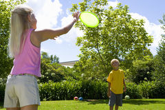 Boy and girl (9-11) playing with flying disc in garden, low angle view Stock Photos