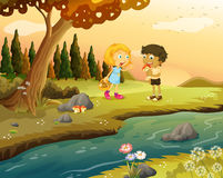 A boy and a girl playing at the forest near the riverbank Royalty Free Stock Photo