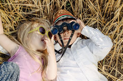 Boy and girl playing in grass with binoculars Stock Photo