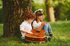 Boy and girl playing guitar in summer park stock image