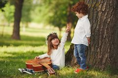 Boy and girl playing guitar in summer park Stock Photography