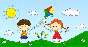 A boy and a girl playing in the meadow and launching a kite Royalty Free Stock Image