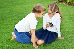 Boy and girl playing on a mobile phone. While sitting on green grass Royalty Free Stock Image