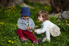 Boy and girl playing with mobile phone Stock Images