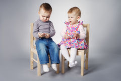 Boy and girl playing with mobile phones Stock Photos