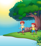 A boy and a girl playing near the giant tree Royalty Free Stock Photography