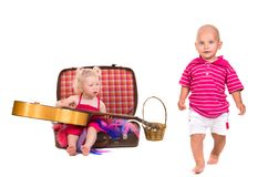 Boy and girl playing near a suitcase, a guitar Royalty Free Stock Image
