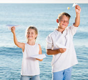 Boy and girl playing origami planes Stock Photo