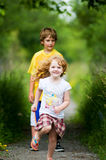 Boy and girl playing outdoors in summer. Brother and sister playing outdoors in the summertime Royalty Free Stock Images