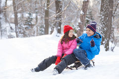 Boy and girl playing outside on sledges. Royalty Free Stock Image