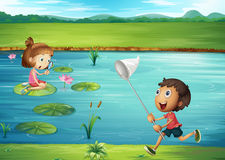 Boy and girl playing by the pond Royalty Free Stock Image