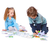 Boy and girl are playing with puzzle. Isolated on a white background Royalty Free Stock Photography