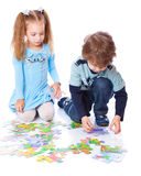 Boy and girl are playing with puzzle Royalty Free Stock Image
