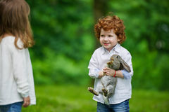 Boy and girl playing with rabbit Stock Photo