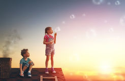 Boy and girl playing on the roof. Happy childhood! boy and girl playing on the roof. child blowing soap bubbles Stock Photography
