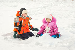 Boy and girl playing on the snow Stock Images