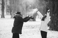 Boy and girl playing with snow. In snow-covered park Stock Images