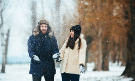 Boy and girl playing with snow. In snow-covered park Stock Photos